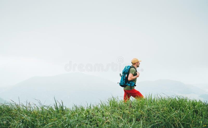 Sidan sköt av fotvandraremannen som går vid den dimmiga molniga väderbergskedjabanan med ryggsäcken Aktiv sund sportfotvandring royaltyfri foto
