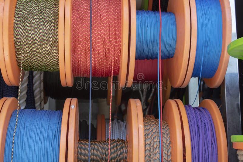 Sidan sköt av raderna som sloggs in runt om rullen Rep i vita, blåa, röda gula färger Sändnings och rep som används i bransch royaltyfria foton
