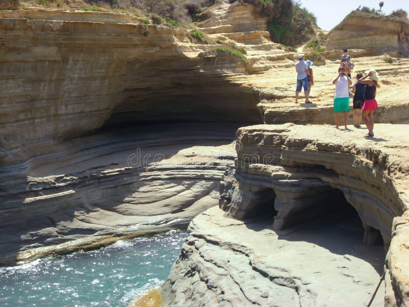 Sidari, Корфу, Греция - 8-ое июня 2013: Туристы имея потеху на любов ` канала d на острове Корфу - Kerkyra - пляж Sidari стоковая фотография rf