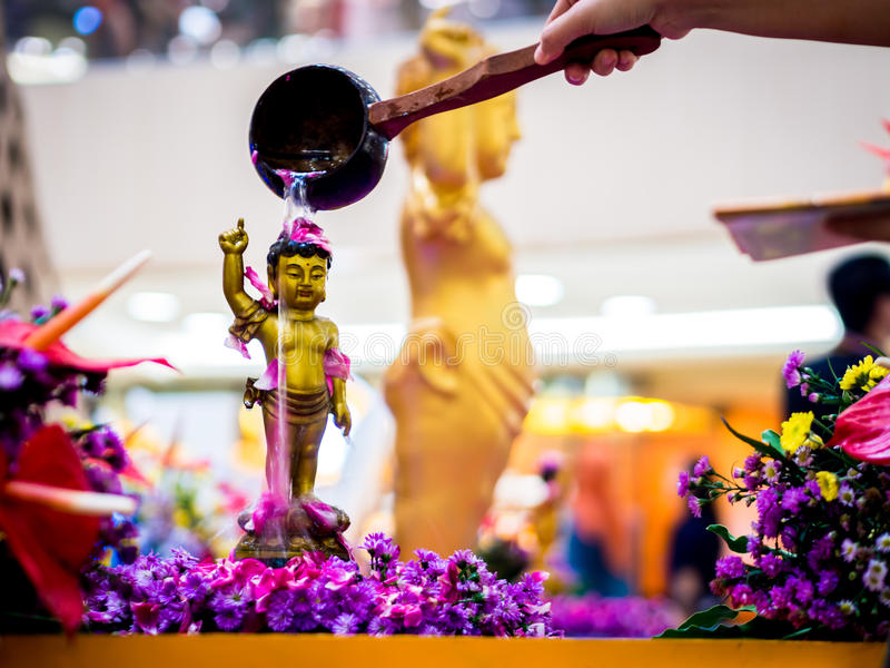 Siddhartha Gautama Buddha Sculpture Flushed by Water and Flower.  royalty free stock image