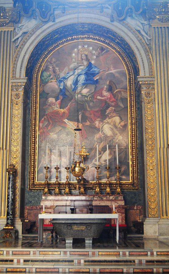 Side altar of St Peters Basilica in Vatican. Vatican, Italy - October 11, 2014. Side altar of St Peters Basilica in Vatican, with religious painting, candles and stock photos