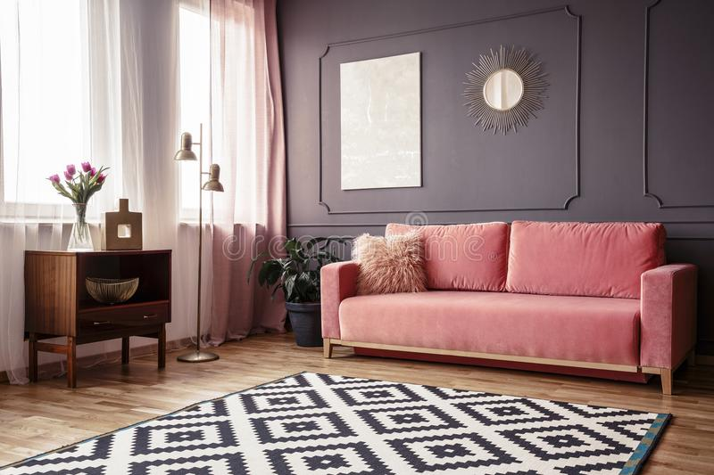 Side angle of a living room interior with a powder pink sofa, pa. Tterned rug, wooden cabinet and wall decorations royalty free stock photography