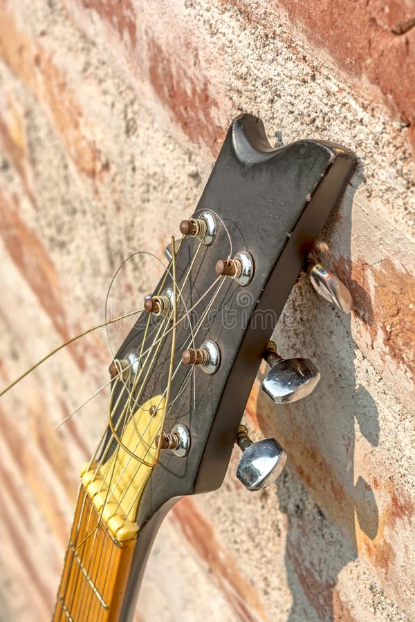 Side view of Six-string acoustic guitar headstock on wall background royalty free stock image