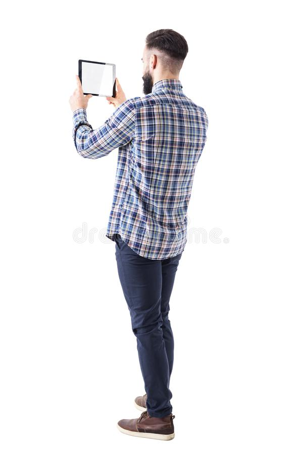 Side back view of young business bearded man holding pad tablet computer taking photo royalty free stock photos