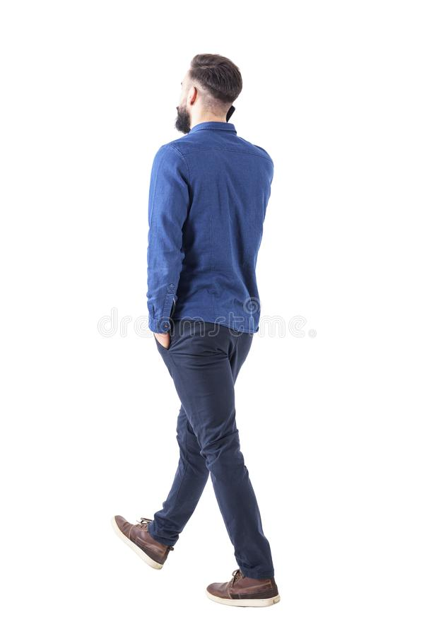 Side back view of young smart casual business man talk on the cellphone walking away. Full body isolated on white background royalty free stock image