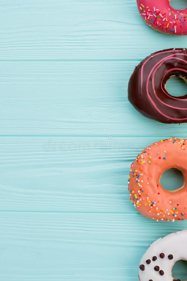 Side border of assorted donuts and copy space. Colorful donuts on blue wooden background. Space for text royalty free stock image