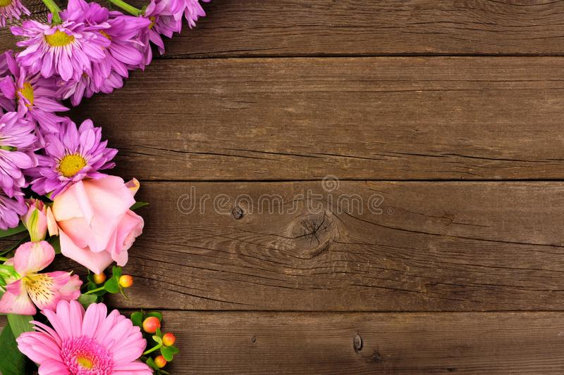 Side border of pink and purple flowers against a rustic wood background stock photo