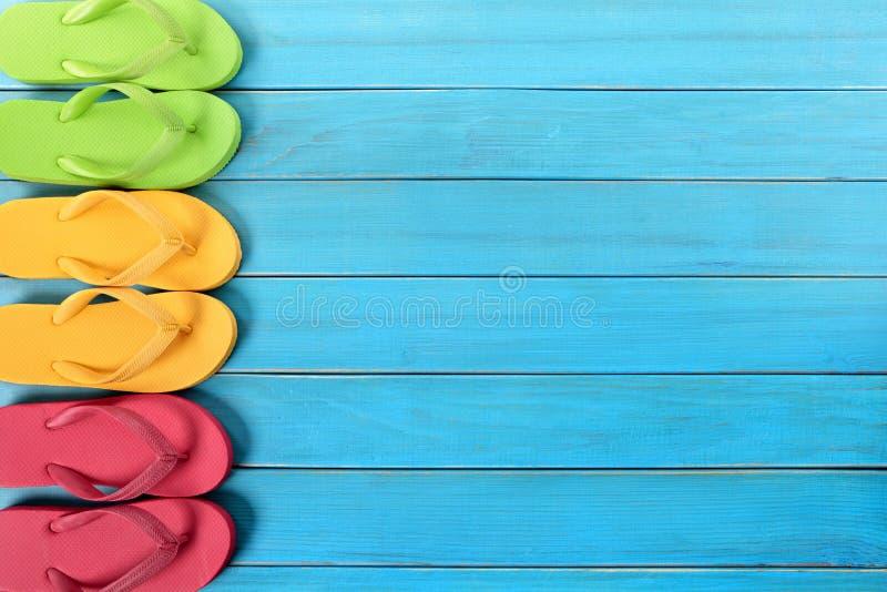 Side border row of flip-flops on blue background wood beach deck stock image