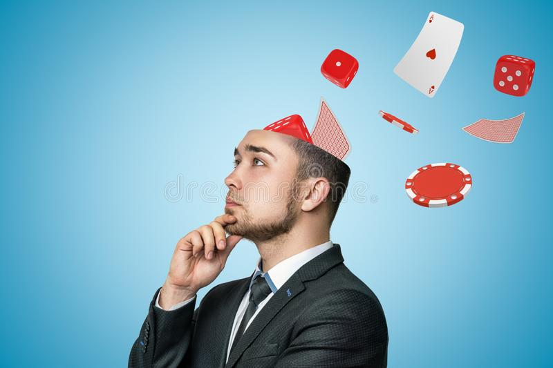 Side close-up of young handsome businessman rubbing chin, upper part of head cut off, with cards, dice and casino chips stock photo