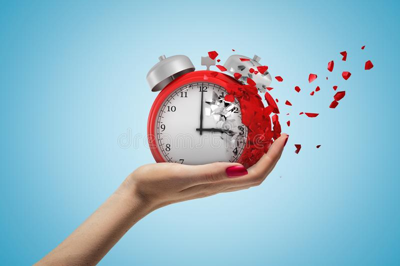 Side closeup of woman`s hand facing up and holding red retro alarm clock that is dissolving into small pieces on light. Blue background. Run out of time. Fail stock photos