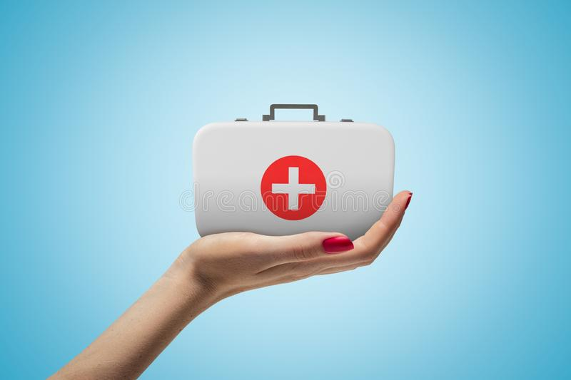 Side closeup of woman`s hand facing up and holding small medical bag on light blue gradient background. royalty free stock photo