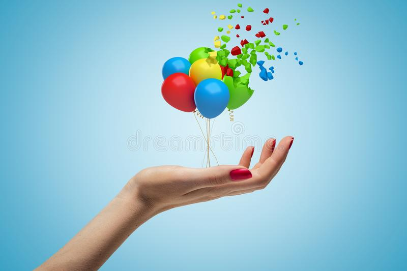 Side closeup of woman`s hand facing up and holding tiny bundle of colorful balloons that are dissolving in pieces on top. On light blue background. Holidays royalty free stock photo