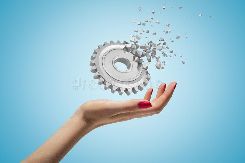 Side closeup of woman`s hand facing up and levitating gearwheel that is already dissolving into pieces on light blue stock images