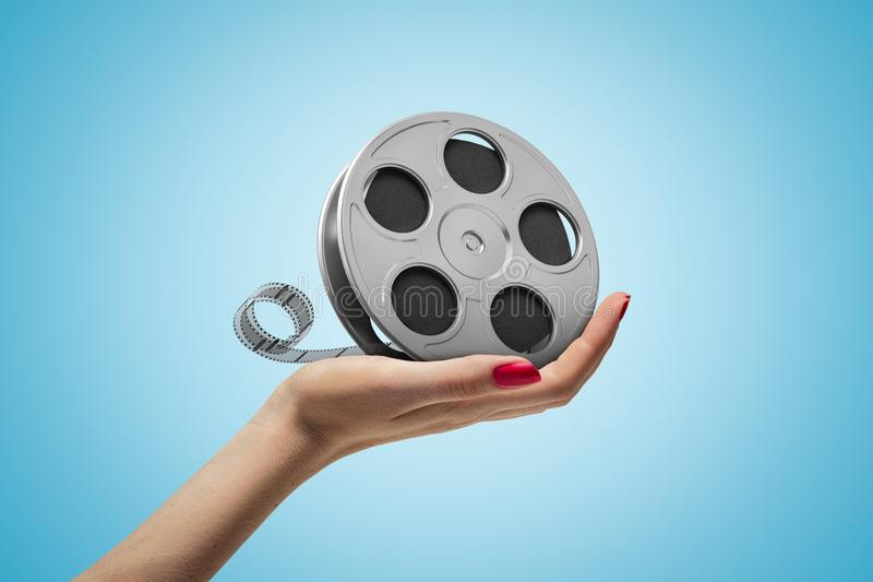 Side closeup of woman`s hand holding film reel on light blue gradient background. royalty free stock photography