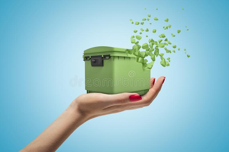 Side closeup of woman`s hand holding green trash can starting to dissolve in little pieces on light blue gradient royalty free stock photos