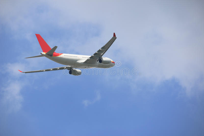 Side of commercial plane on blue sky royalty free stock photography