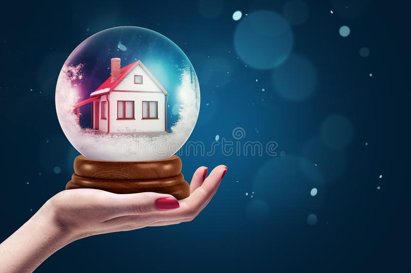 Side crop close-up of female`s hand facing up holding crystal ball with house inside. royalty free stock images