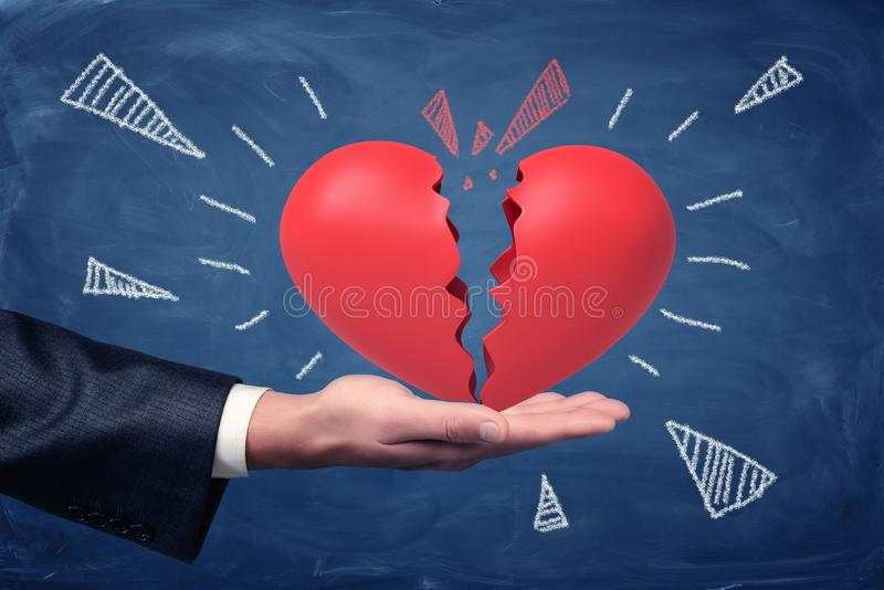 Side crop close-up of man`s hand facing up and holding big red heart split into halves on blackboard background. stock photography