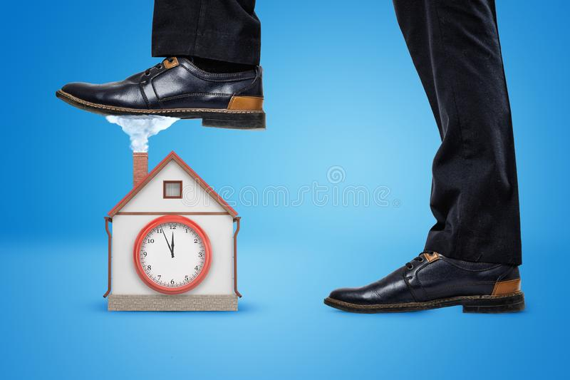 Side crop close-up of man`s legs, one foot raised to step on a little house with a big clock on the wall. stock images