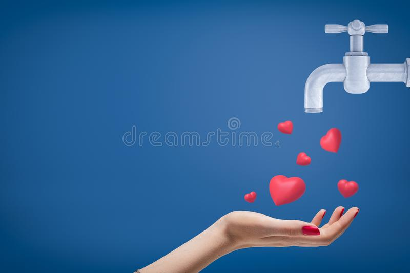 Side crop close-up of woman`s hand facing up and catching cute red hearts coming from grey tap on blue background with a stock image
