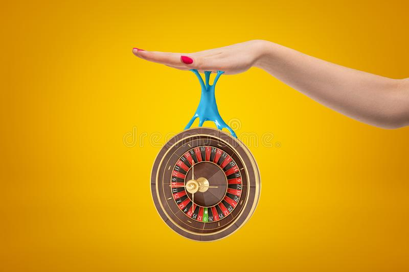 Side crop closeup of woman`s hand holding casino wheel that is hanging down on blue sticky slime stuck to her palm. stock photography