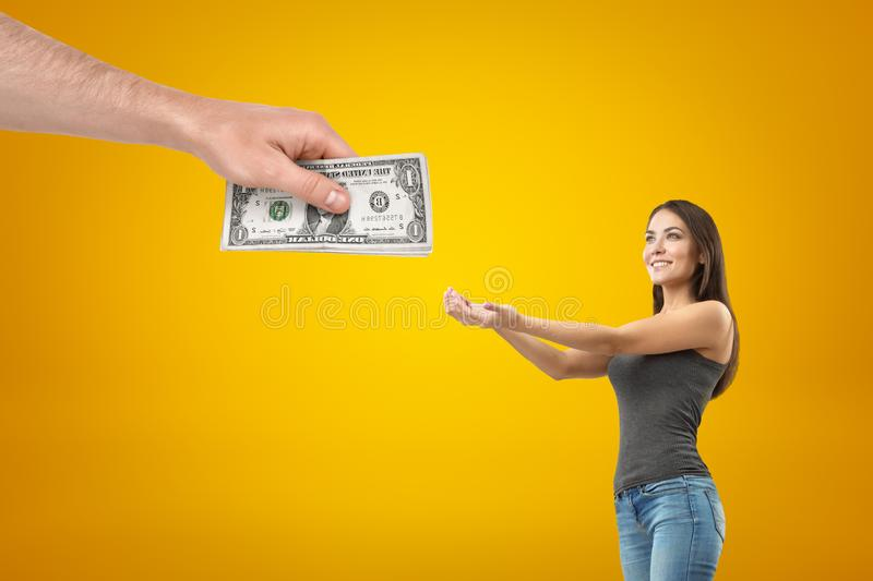 Side crop view of young pretty girl in casual clothes holding out hands to take money from big man`s hand. stock images