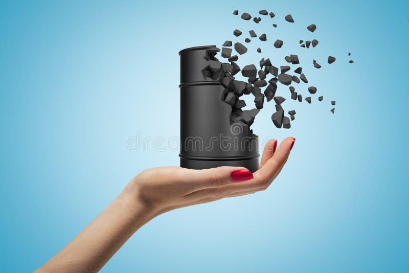 Side fermeture de la main de la femme face vers le haut et tenant un petit tonneau de métal noir qui commence à se dissoudre en m photo stock