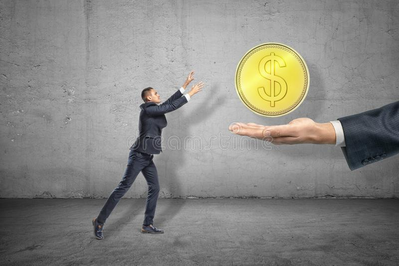 Side full length view of little businessman reaching out for big gold coin levitated above huge hand emerging from right stock image