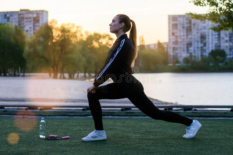 Side half profile view photo portrait of slim skinny muscular young pretty attractive charming nice lovely healthy young lady girl. In sportwear doing stock images