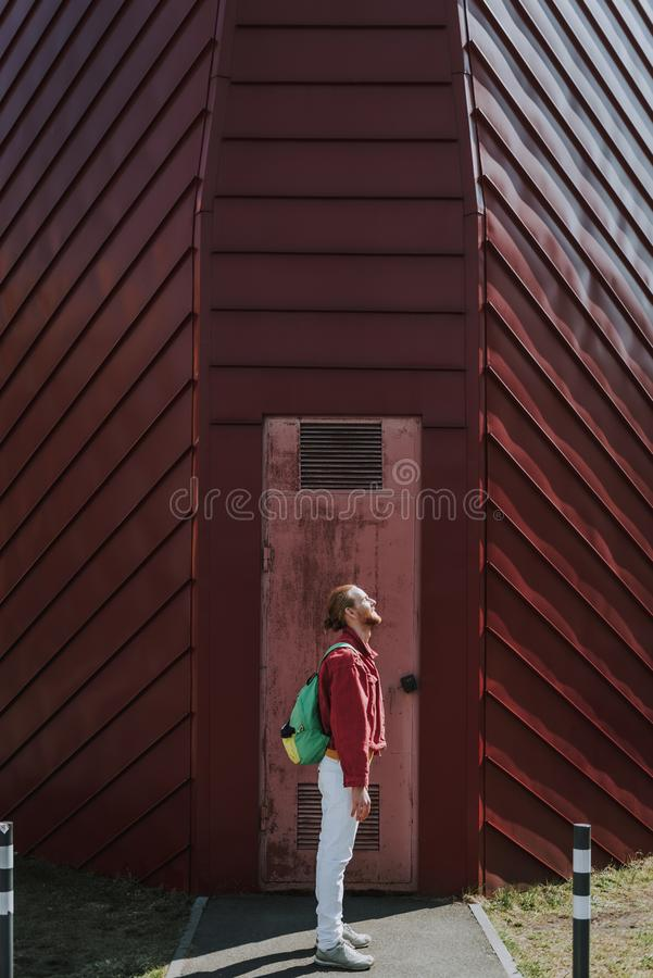 Side on hipster man staying on city building view. Urban lifestyle concept. Full length side on portrait of young smiling hipster guy staying on red building royalty free stock images