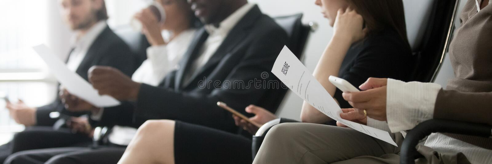 Side horizontal photo multiracial people sitting in queue waiting interview. Horizontal side photo multinational applicants businesspeople sitting in queue royalty free stock photography