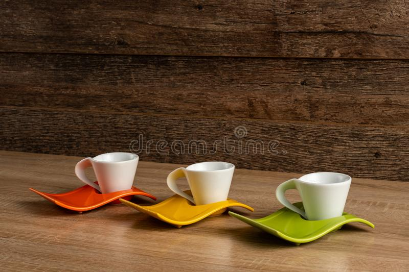 Side left to right inclined view of white coffee cups place on three colours plates. royalty free stock photos