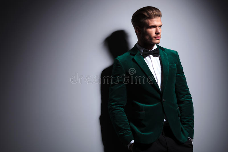 Side of a man in green velvet elegant suit. Relaxed young fashion model in green velvet elegant suit with neck bow tie looking away from the camera white royalty free stock image