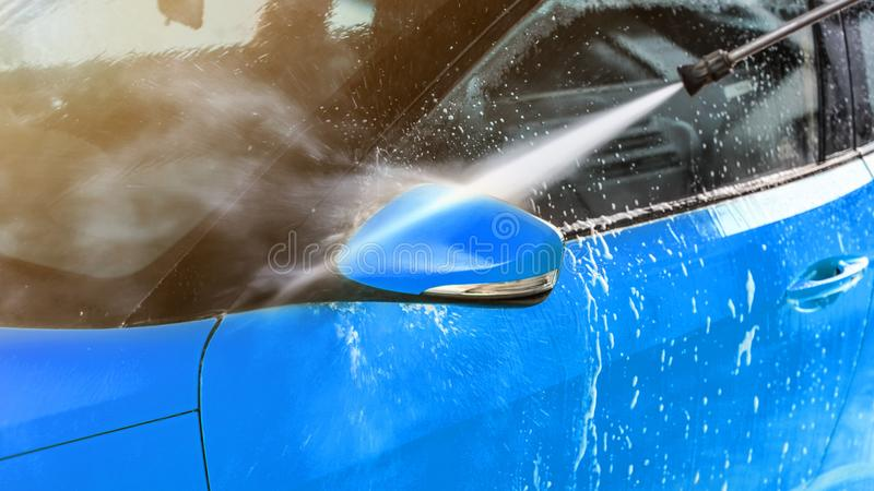 Side mirror of blue car washed in self serve carwash, jet water sprays from high pressure nozzle royalty free stock photos