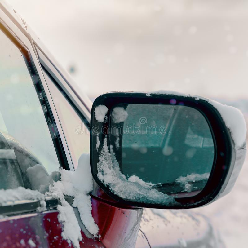A side mirror of a car in the snow on a winter day royalty free stock photo