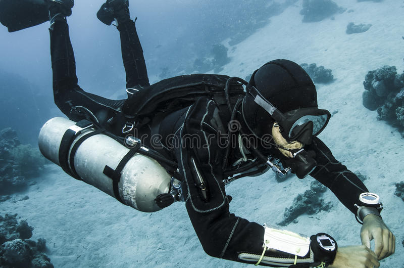 Side mount scuba dives in clear blue water stock photos