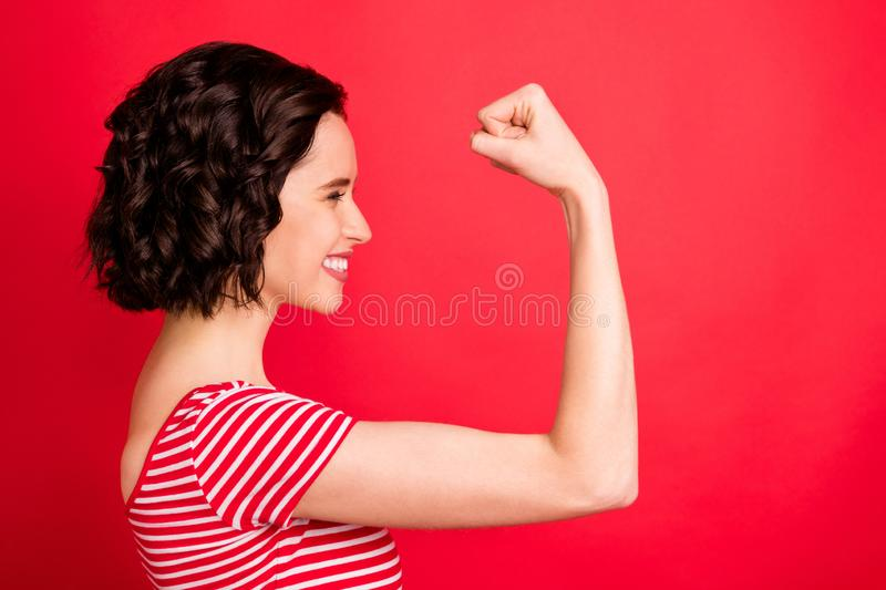 Side photo of gorgeous attractive charming wavy curly girl having just returned home from gym bragging about her muscles. Side photo of gorgeous attractive royalty free stock image