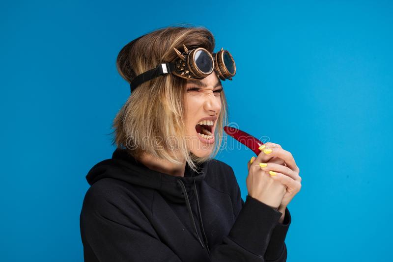 Side portrait of angry steam punk girl with dark hoodie and glasses biting a dark red chilli pepper with attitude stock photos