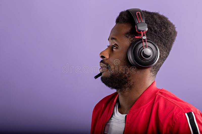 Side portrait of a beautiful afroamerican men in a red sports jacket and headphones on purple background with copy space stock photos