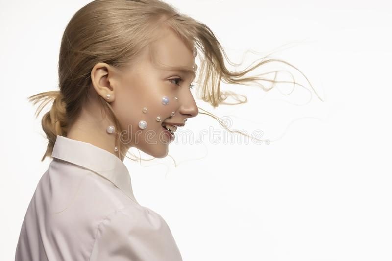 Side portrait of a beautiful blonde teenage girl. Conceptual makeup decorated with white pearls on the face, vanguard hairstyle. stock photos