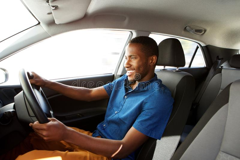 Happy young african man driving a car. Side portrait of happy young african male driver driving a car royalty free stock photography