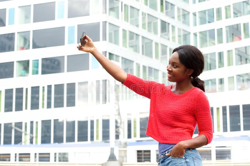 Side of happy young black woman taking selfie photo in the city. Side portrait of happy young black woman taking selfie photo in the city royalty free stock image