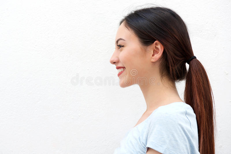 Side portrait of healthy young woman with long hair smiling stock photo