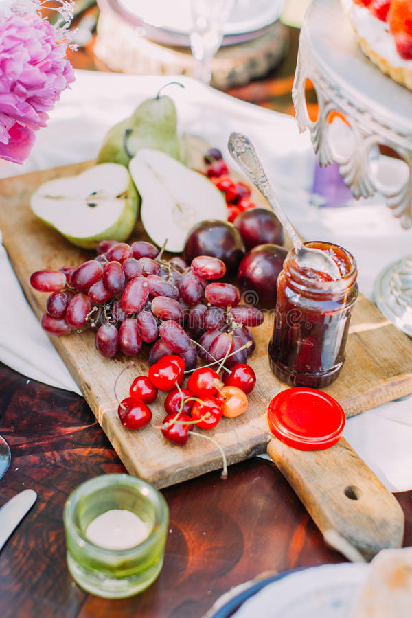 The side portrait of juicy red grapes, cherries, green pears, plums and the bar of jar located on the wooden board near stock photos