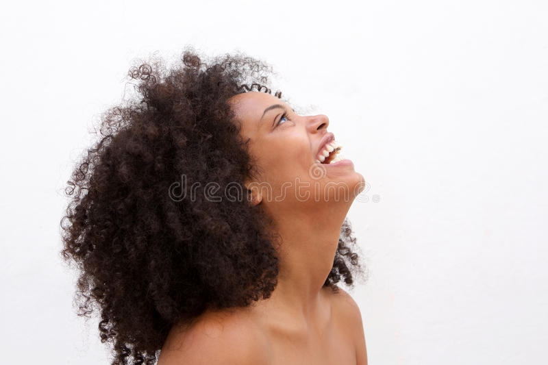 Side portrait of laughing black woman with bare shoulders. Close up e portrait of laughing black woman with bare shoulders stock photo