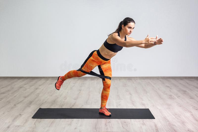 Side portrait view of beautiful young woman wearing black tank top and orange leggings, workout alone against white wall, doing. Yoga or pilates exercise with stock image