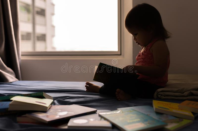 Smart young child reading a book on the bed. royalty free stock images