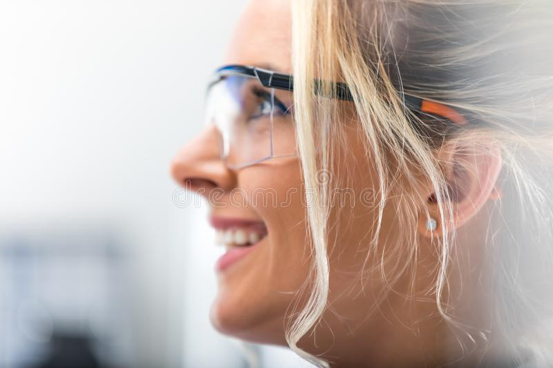 Side portrait of young attractive woman in protective eyeglasses stock photo