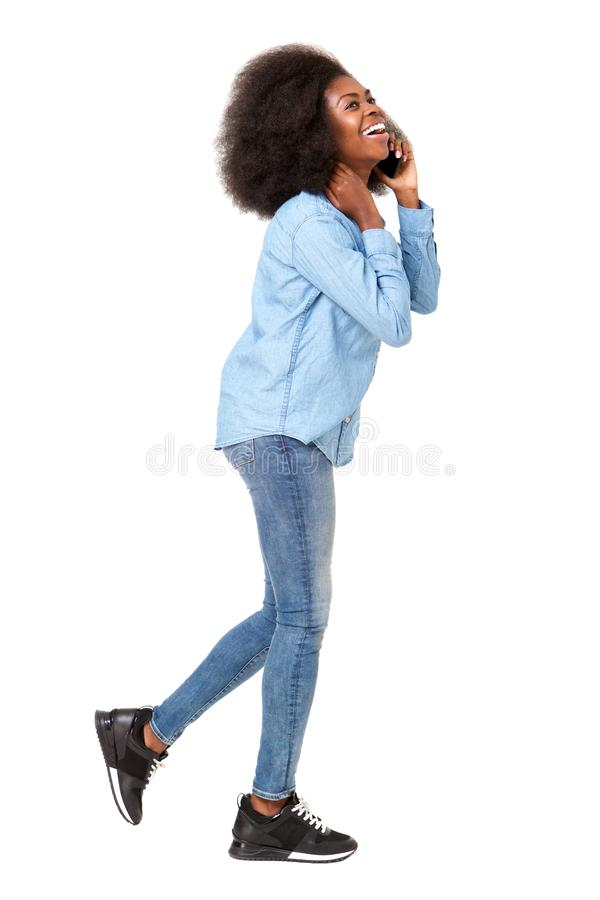 Side portrait of young black woman walking and talking on cellphone royalty free stock photos