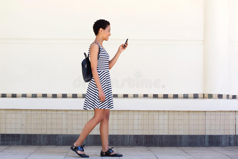Side portrait of young woman walking on with cellphone and bag stock photos